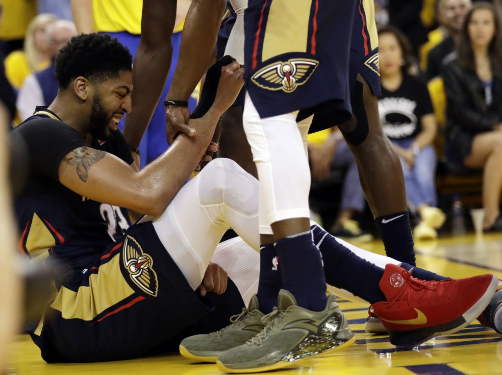 New Orleans Pelicans' Anthony Davis is lifted by teammates after being fouled by the Golden State Warriors during the first half in Game 1 of an NBA b...