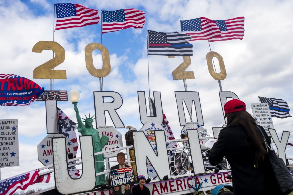 Flags fly high above the Trump Unity Bridge, a mobile float parked outside of the rally's entrance, as thousands of supporters of President Donald J. ...