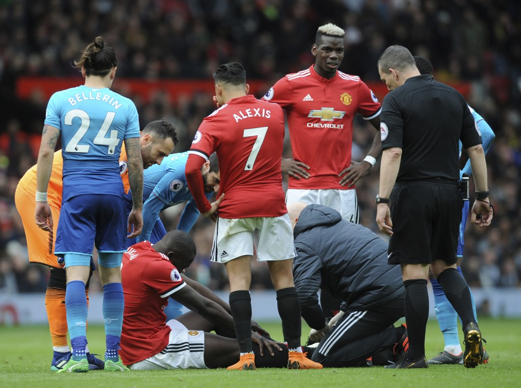 Manchester United's Romelu Lukaku, left down, receives a medical help during the English Premier League soccer match between Manchester United and Ars...