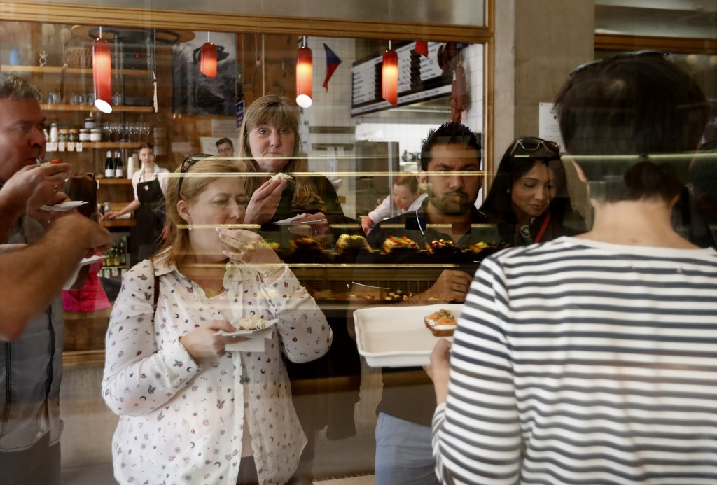 In this picture taken on Tuesday, April 10, 2018, group of tourists gets a taste of open-face sandwiches at bistro Sisters in Prague, Czech Republic. ...