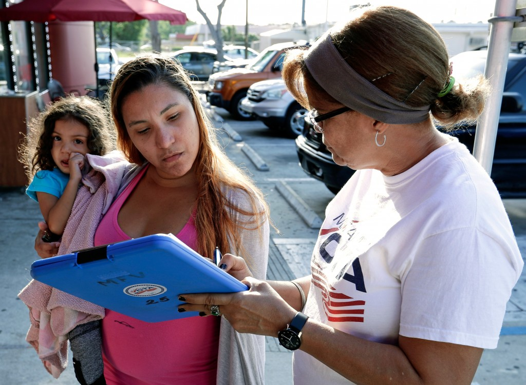 In this April 12, 2018 photo, Michelle Ortiz, who was born in New York to Puerto Rican parents and recently moved to Florida, holds her daughter as sh...