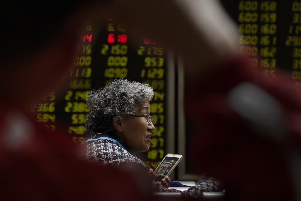 In this April 3, 2018 photo, a woman chats with her friends as they monitor stock prices at a brokerage house in Beijing. Shares were higher in Hong K...