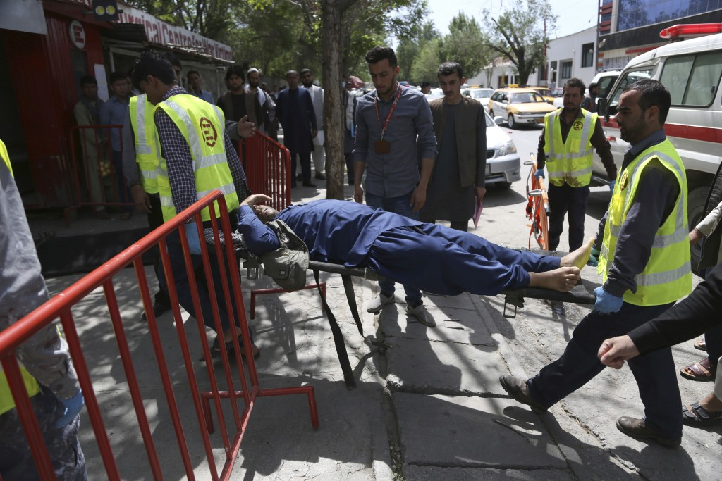 Afghan men carries a wounded man after the second blast in Kabul, Afghanistan, Monday, April 30, 2018. A coordinated double suicide bombing hit centra...