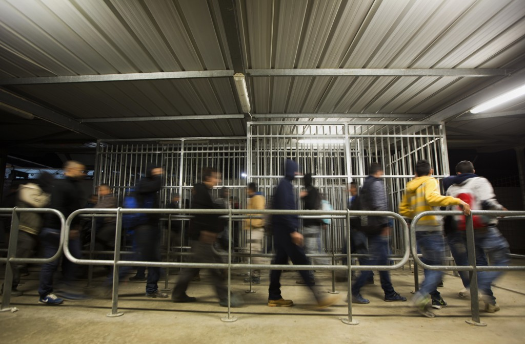 In this March 9, 2017 file photo, Palestinian laborers who work in Israel cross through a checkpoint to enter Israel, near the West Bank village of Ni...