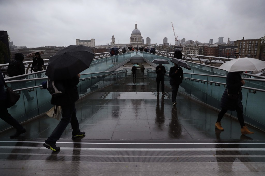 People walk with umbrellas on the Millennium Footbridge on a cold and rainy morning in London, Monday, April 30, 2018. In the background is the dome o...