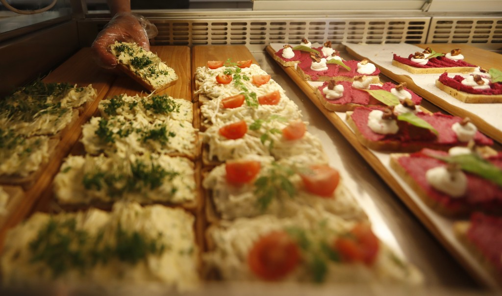 In this picture taken on Tuesday, April 10, 2018, woman adjusts open-face sandwiches at bistro Sisters in Prague, Czech Republic. With an undying popu...