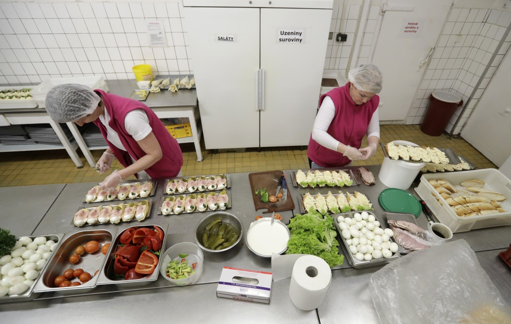 In this picture taken on Thursday, March 1, 2018, women prepare open-face sandwiches at traditional delicatessen Golden Cross in Prague, Czech Republi...