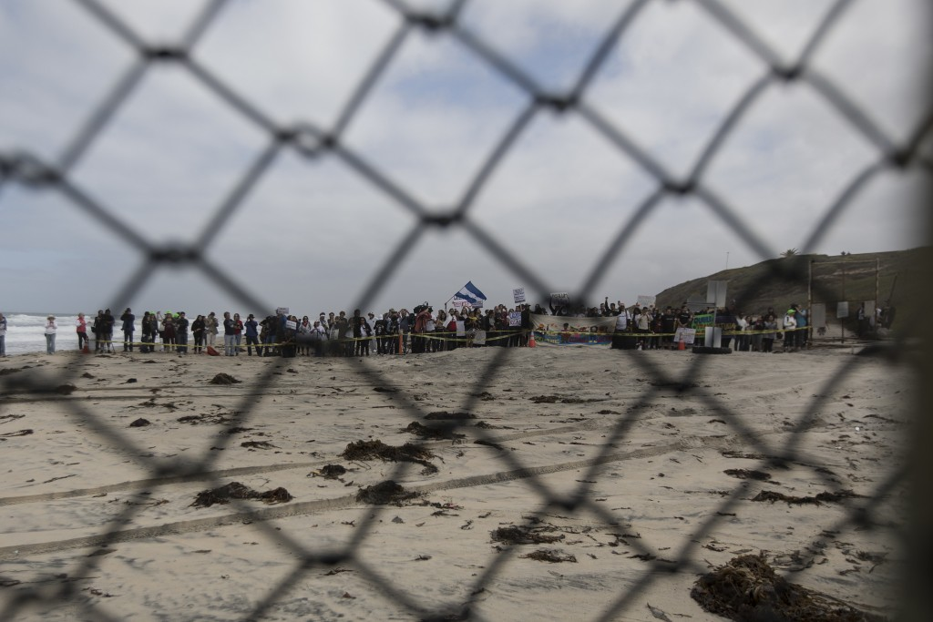 Seen through the border wall, people stand on the U.S. side during a gathering of migrants living on both sides of the border, on the beach where the ...