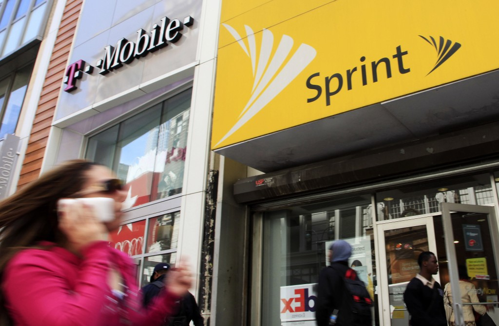 FILE- In this April 27, 2010 file photo, a woman using a cell phone walks past T-Mobile and Sprint stores in New York. T-Mobile and Sprint are trying ...