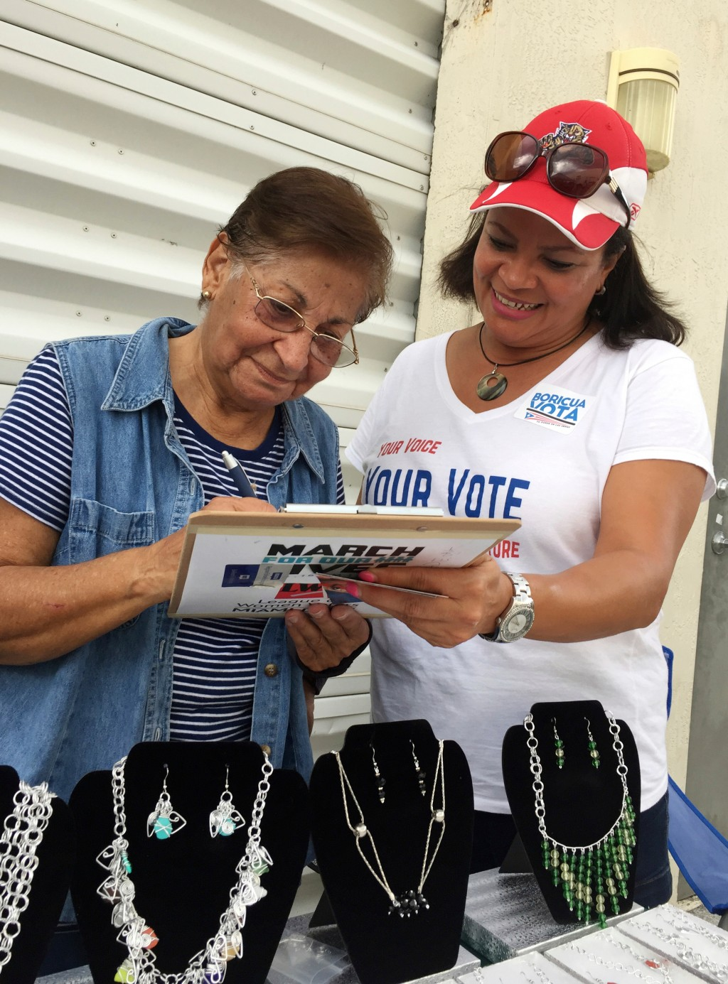 In this April 8, 2018 photo, Marisol Zenteno, right, from The League of Women Voters, registering Aida Merced Lopez, who moved to Miami from Puerto Ri...