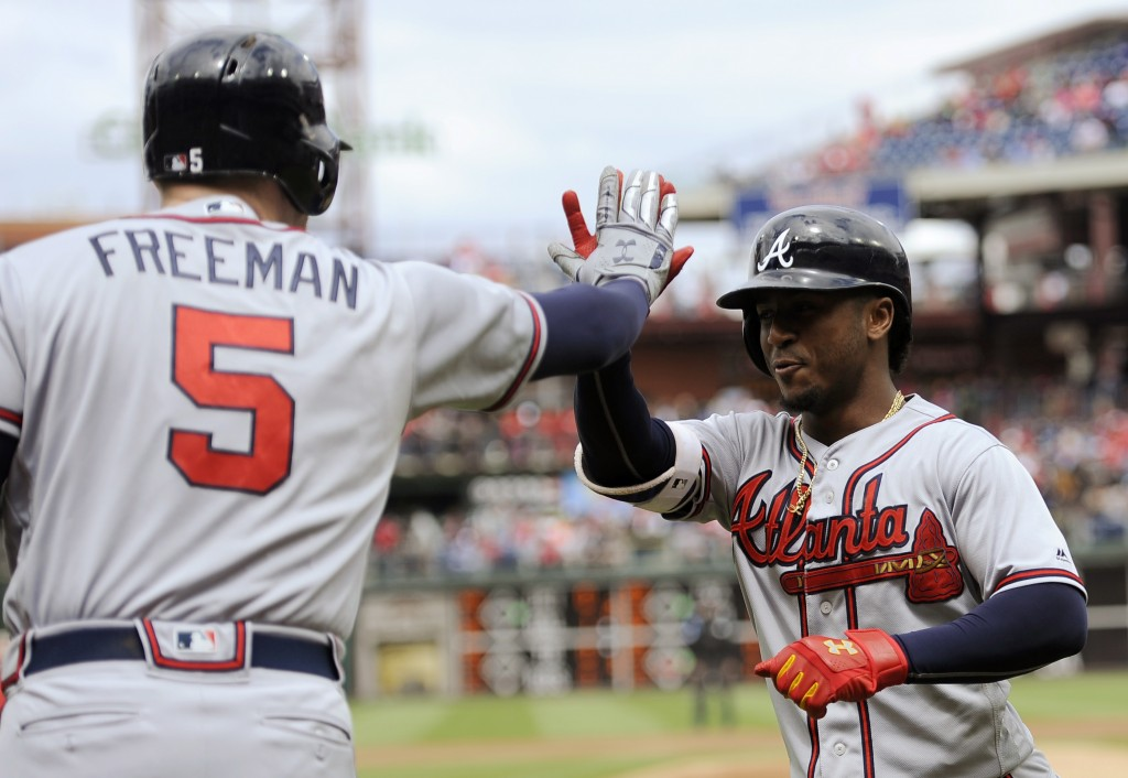 Atlanta Braves' Ozzie Albies, right, celebrates with Freddie Freeman after he scores on a solo home run in the first inning of a baseball game against...