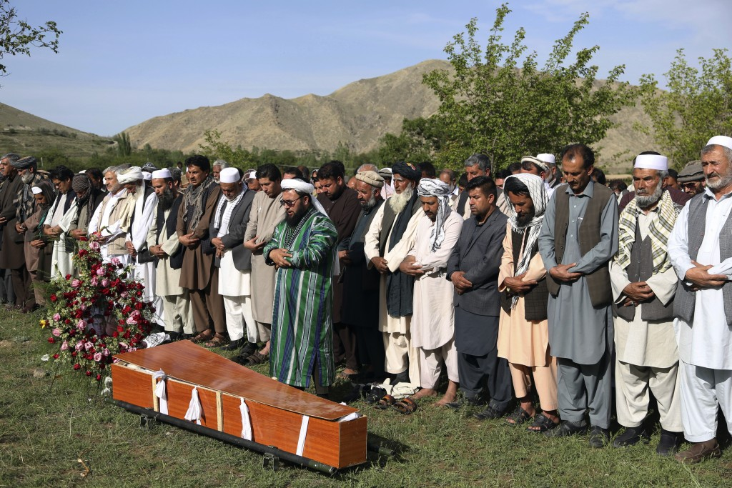 Relatives, colleagues and friends offer funeral prayers behind the body of AFP chief photographer, Shah Marai, who was killed in today's second suicid...