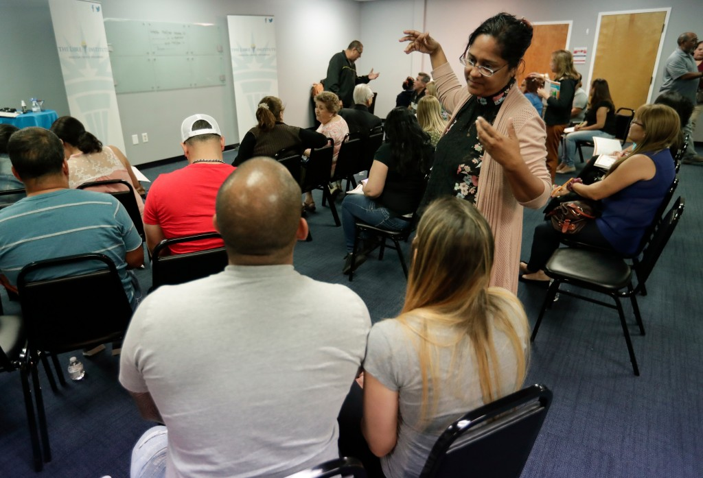 In this April 12, 2018 photo, English teacher Michelle Pacheco, standing, speaks with latino students in Orlando, Florida. A conservative effort is co...
