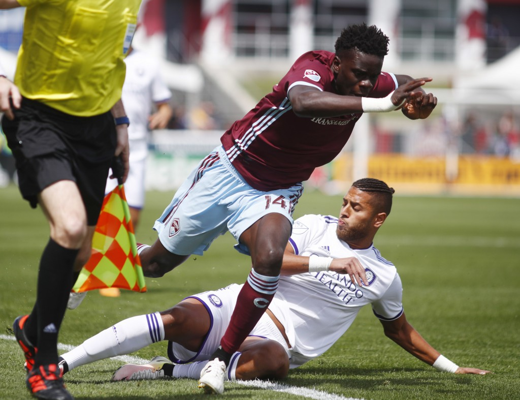 Colorado Rapids forward Dominique Badji, top, tumbles over Orlando City defender Amro Tarek after losing the ball in the first half of an MLS soccer m...