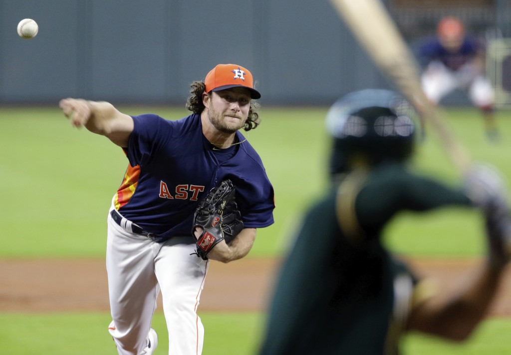 Houston Astros' starting pitcher Gerrit Cole throws against Oakland Athletics' shortstop Marcus Semien (10) during the first inning of a baseball game...