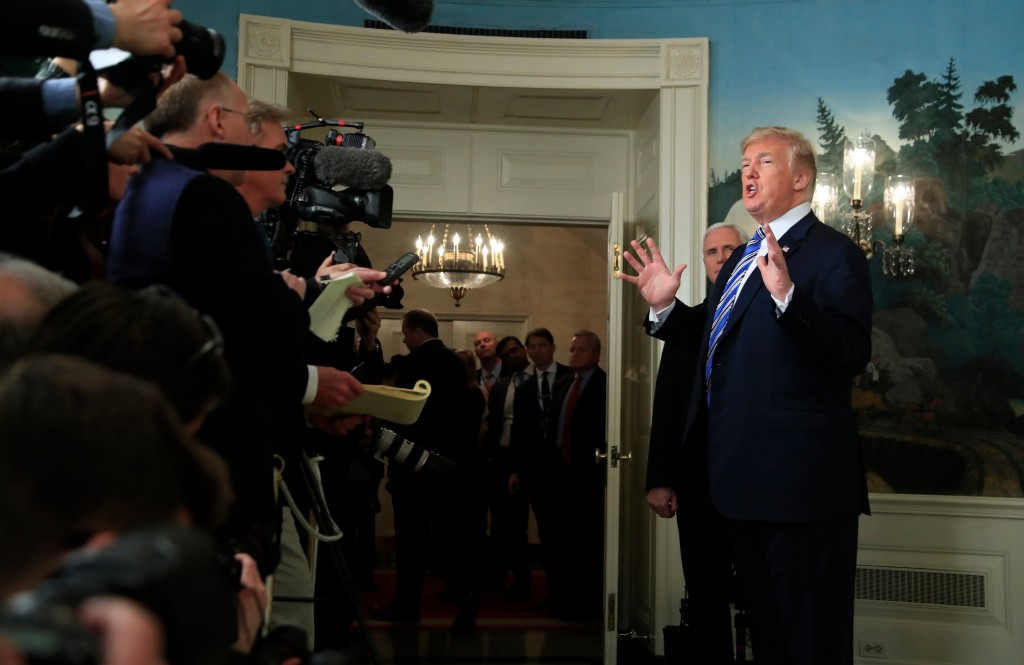 FILE - In this March 23, 2018 file photo, President Donald Trump responds to reporters' questions in the Diplomatic Room of the White House in Washing...