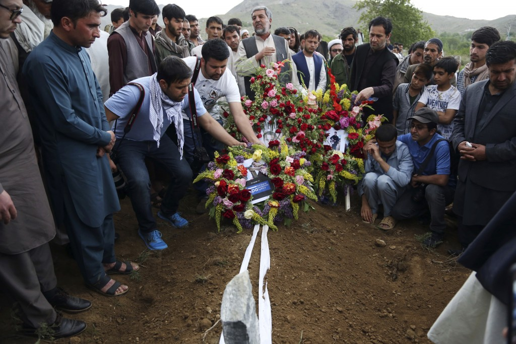 Relatives, colleagues and friends puts flowers on the grave of AFP chief photographer, Shah Marai, who was killed in today's second suicide attack, in...