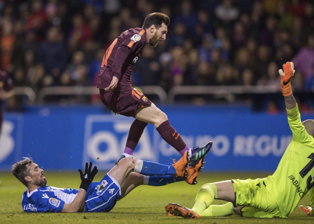 Barcelona's Lionel Messi, center, scores the fourth goal during a Spanish La Liga soccer match between Deportivo and Barcelona at the Riazor stadium i...