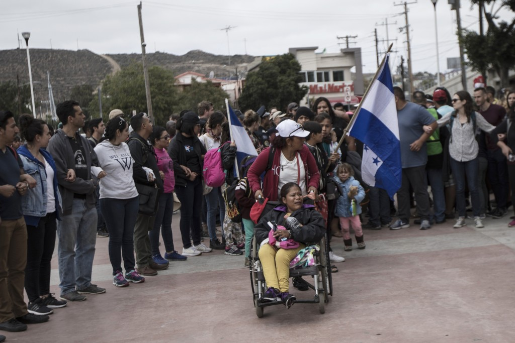Members of a Central American family traveling with a caravan of migrants prepare to cross the border and apply for asylum in the United States, in Ti...