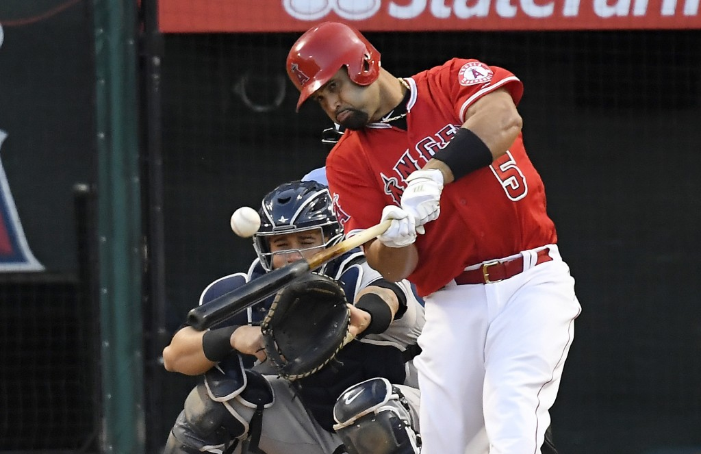 Los Angeles Angels' Albert Pujols hits a single as New York Yankees' Gary Sanchez watches during the sixth inning of a baseball game, Sunday, April 29...