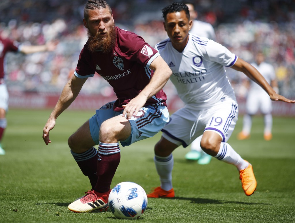 Colorado Rapids midfielder Enzo Martinez, left, pursues the ball with Orlando City defender Yoshimar Yotun in the first half of an MLS soccer match Su...