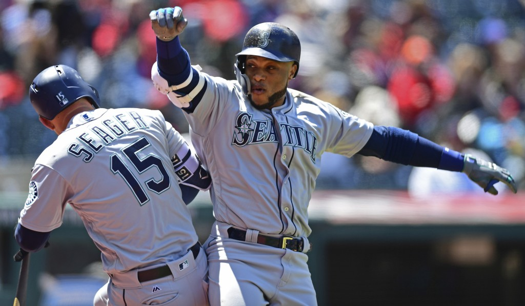 Seattle Mariners' Robinson Cano, right, celebrates with Kyle Seager after hitting a two-run home run off Cleveland Indians starting pitcher Josh Tomli...