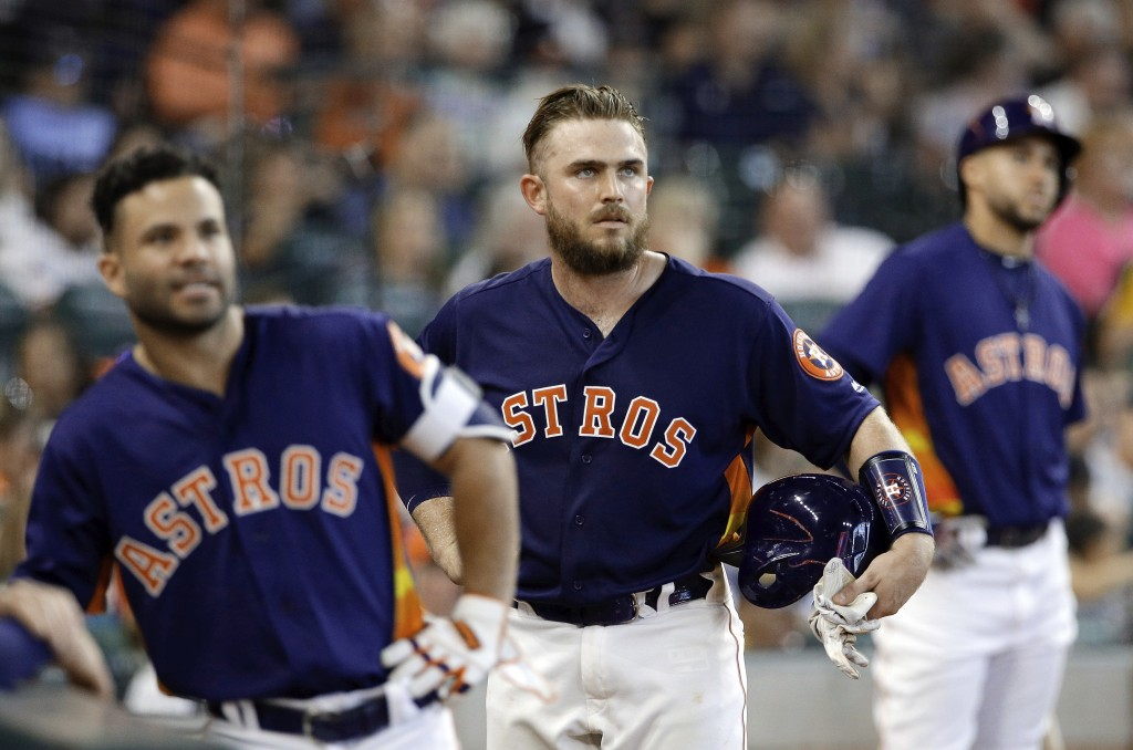 Houston Astros' Jose Altuve, Max Stassi and George Springer watch the video board on the fan interference call on the home run hit by Stassi in the fi...