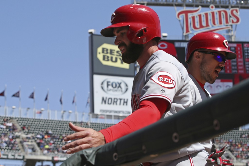 Cincinnati Reds' Jose Peraza is greeted at the dugout after he scored on a hit by Eugeniio Suarez in the first inning of a baseball game against the M...