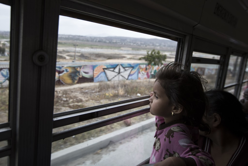 A Central American child who is traveling with a caravan of migrants, peers at the border wall from a bus carrying the group to a gathering of migrant...