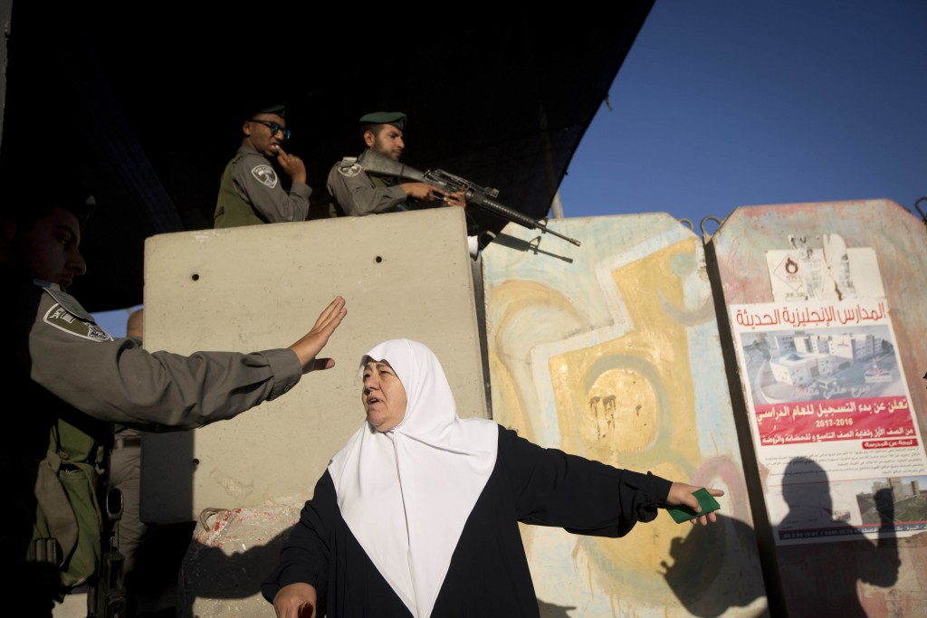 File - In this Friday, June 17, 2015 file photo, Israeli border police officers stand guard as a Palestinian woman waits to cross the Qalandia checkpo...
