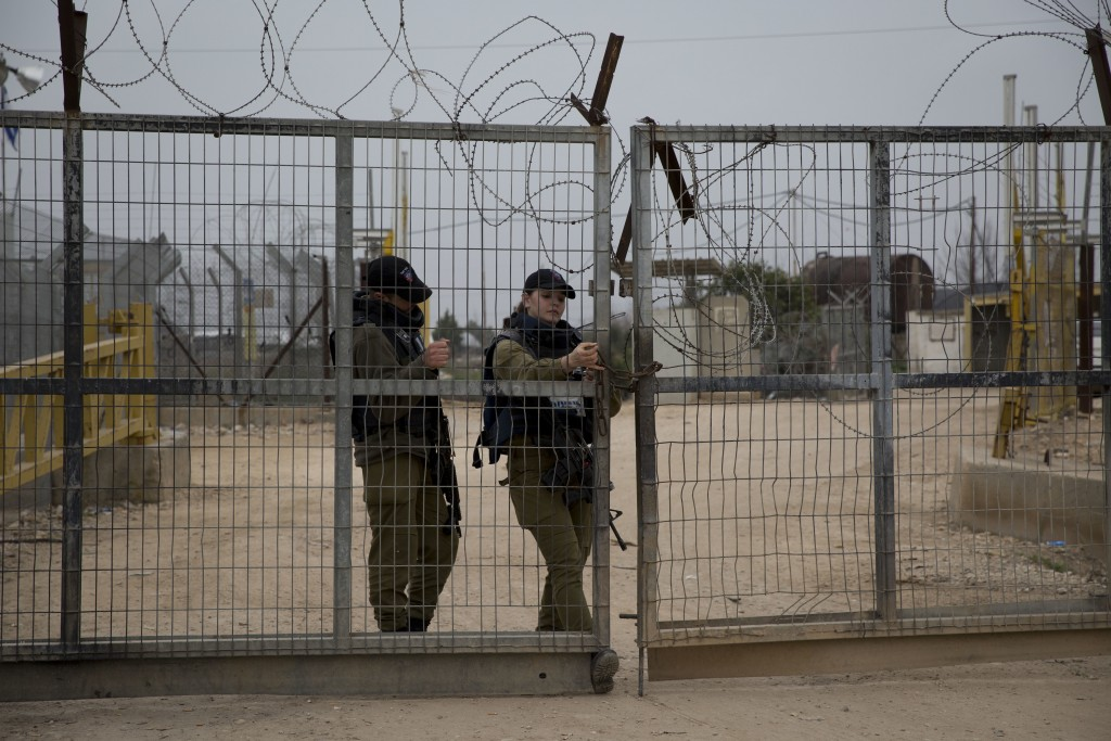 In this Sunday, Feb. 11 2018 photo, Israeli soldiers close the gate of the Israeli separation barrier in the village of Habla, near the West Bank city...
