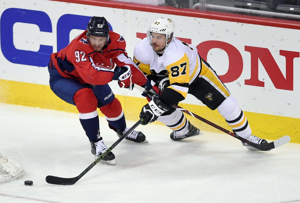 Pittsburgh Penguins center Sidney Crosby (87) skates with the puck against Washington Capitals center Evgeny Kuznetsov (92), of Russia, during the thi...