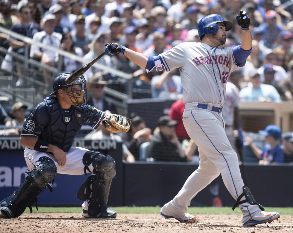New York Mets' Adrian Gonzalez, right, hits a two-run double as San Diego Padres catcher A.J. Ellis looks on during the third inning of a baseball gam...