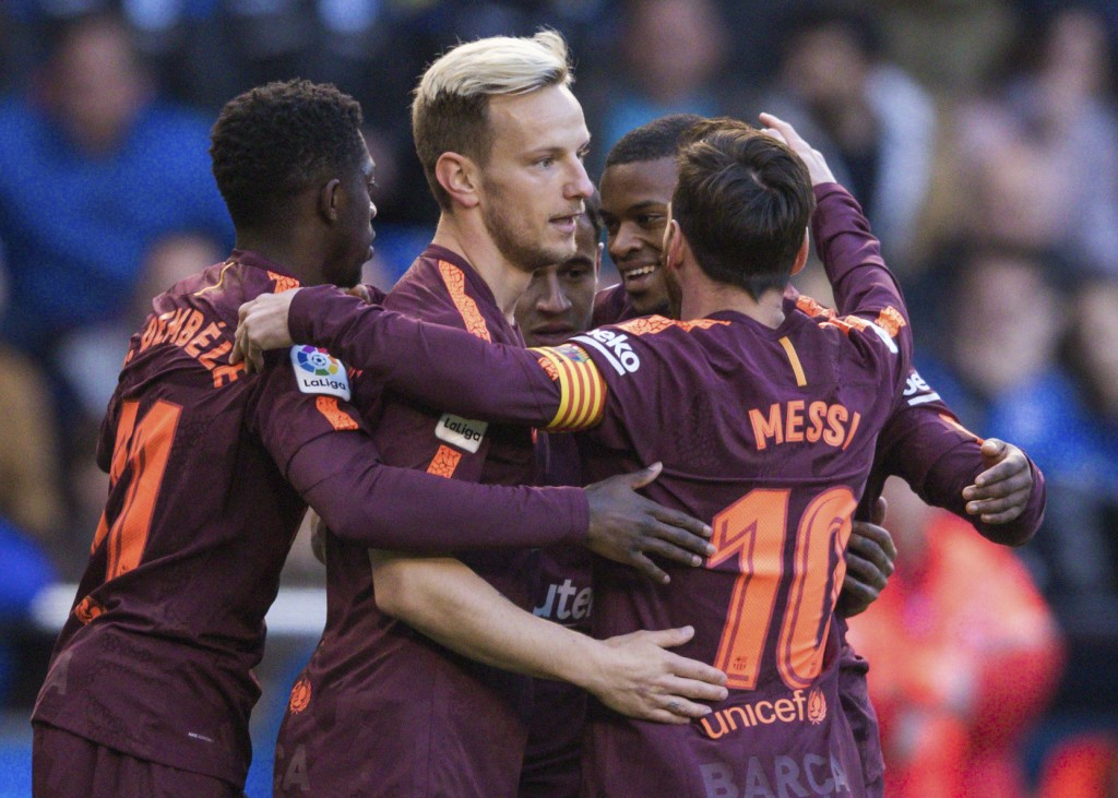 Barcelona's Philippe Coutinho, background center, is congratulated by teammates after scoring a goal during a Spanish La Liga soccer match between Dep...