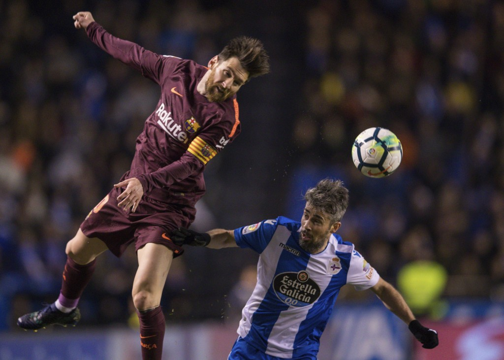 Barcelona's Lionel Messi, left, challenges for the ball with Deportivo's Luisinho during a Spanish La Liga soccer match between Deportivo and Barcelon...