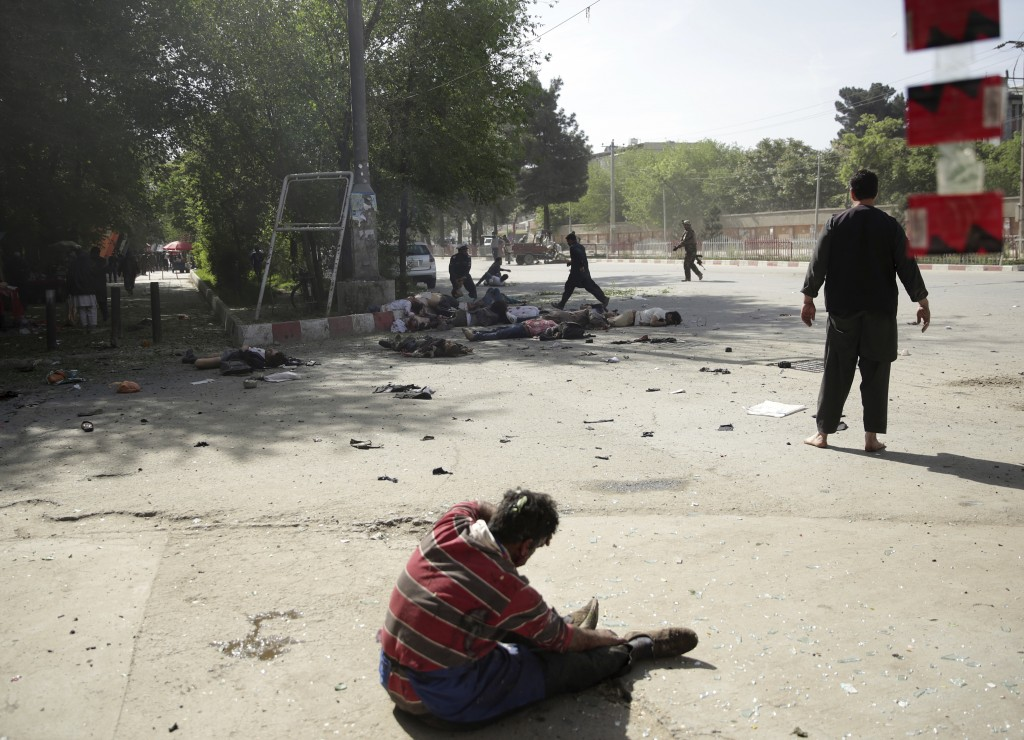 A wounded man sits on the ground after explosions, in Kabul, Afghanistan, Monday, April 30, 2018. A coordinated double suicide bombing hit central Kab...