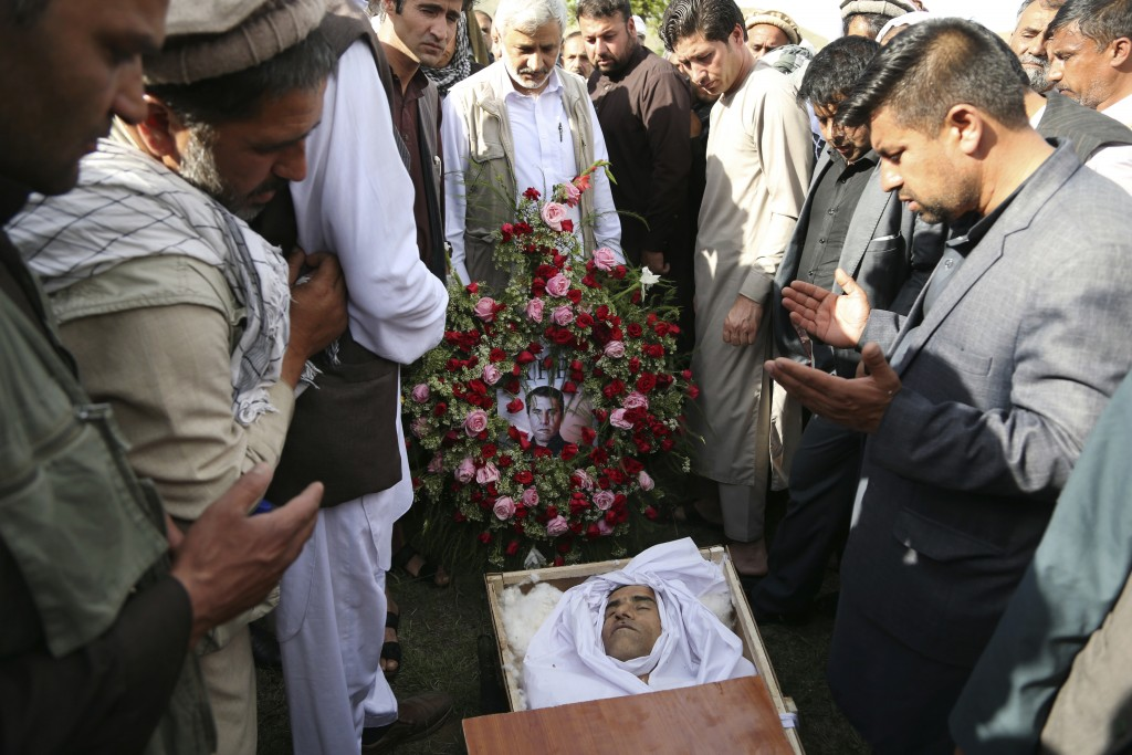 Relatives, colleagues and friends pray next to the body of AFP chief photographer, Shah Marai, who was killed in today's second suicide attack in Guld...