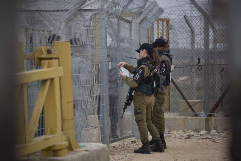 In this photo taken on Sunday, Feb. 11 2018, Israeli soldiers check Palestinians papers to enter their farms in the village of Habla, near the West Ba...