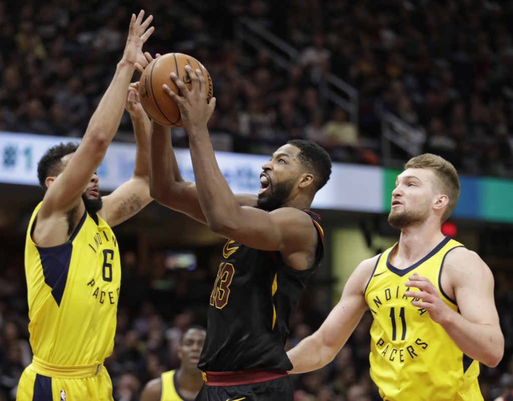 Cleveland Cavaliers' Tristan Thompson, center, shoots between Indiana Pacers' Cory Joseph, left, and Domantas Sabonis, from Lithuania, in the first ha...