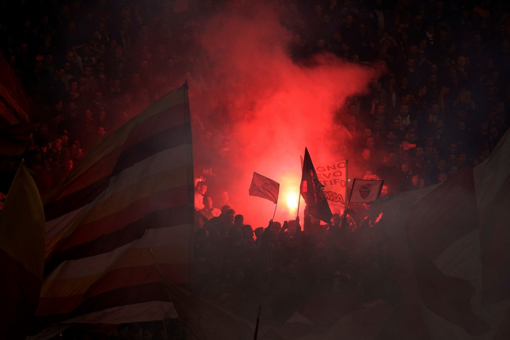 FILE - In this April 10, 2018 file photo, Roma fans set off flares during the Champions League quarterfinal second leg soccer match between between Ro...