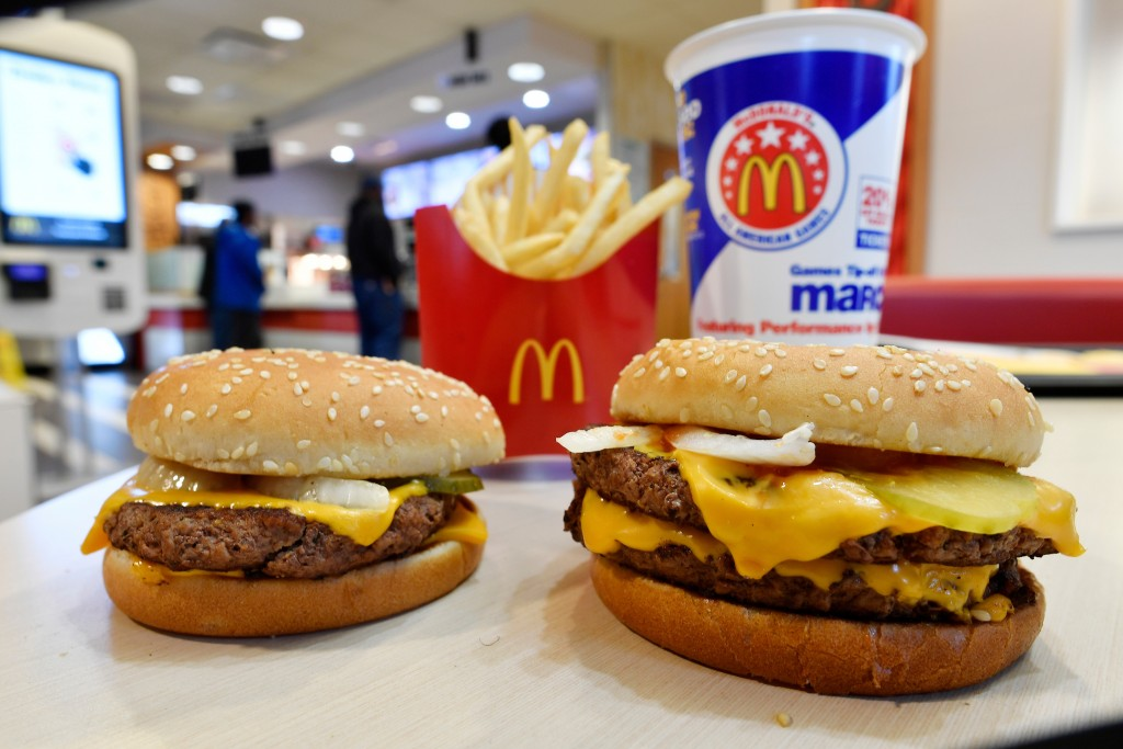 FILE- In this March 6, 2018, file photo, a McDonald's Quarter Pounder, left, and Double Quarter Pound burger is shown with fresh beef in Atlanta. McDo...