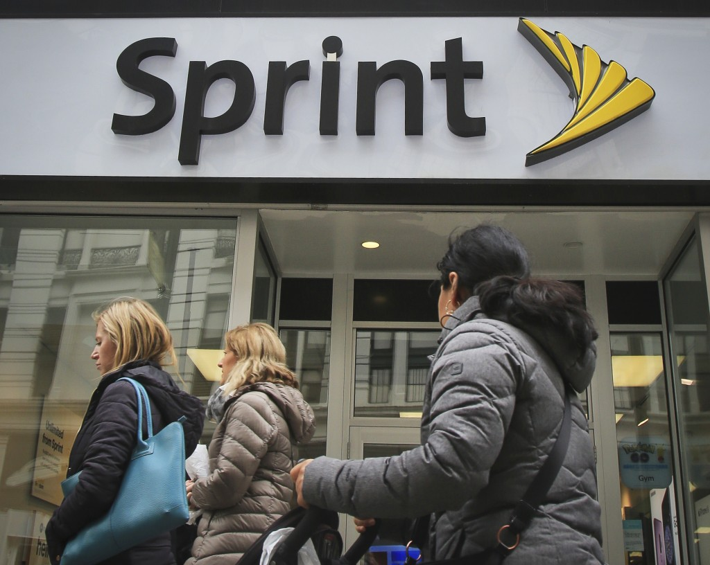 People walk past a Sprint store in New York's Herald Square, Monday, April 30, 2018. Consumer advocacy groups are worried that T-Mobile's bid for Spri...