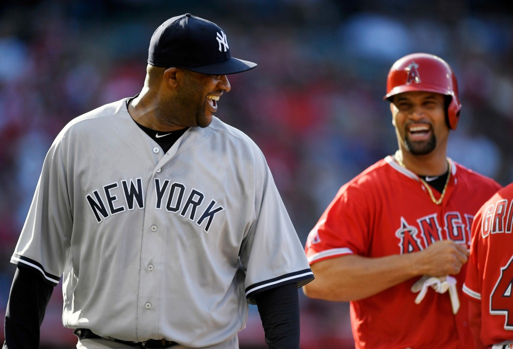 New York Yankees starting pitcher CC Sabathia, left, and Los Angeles Angels' Albert Pujols laugh after Pujols grounded out to Sabathia during the firs...