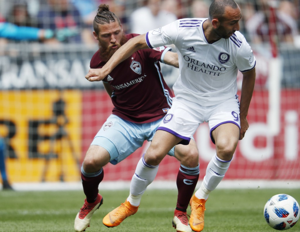 Colorado Rapids midfielder Enzo Martinez, left, battles for control of the ball with Orlando City forward Justin Meram in the first half of an MLS soc...