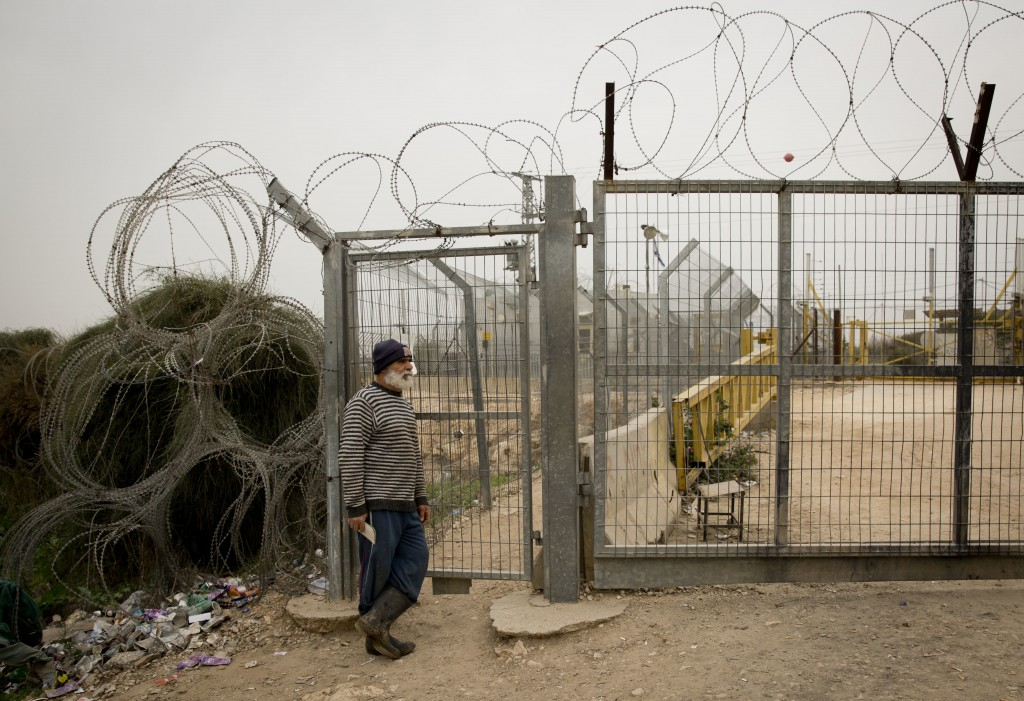In this Feb. 11 2018 photo, a Palestinian waits for Israeli soldiers to open the barrier gate of the to enter his farm in the village of Habla, near t...