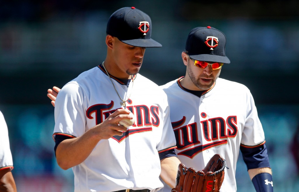 Minnesota Twins pitcher Jose Berrios, left, is consoled by second baseman Brian Dozier in the third inning of a baseball game against the Cincinnati R...