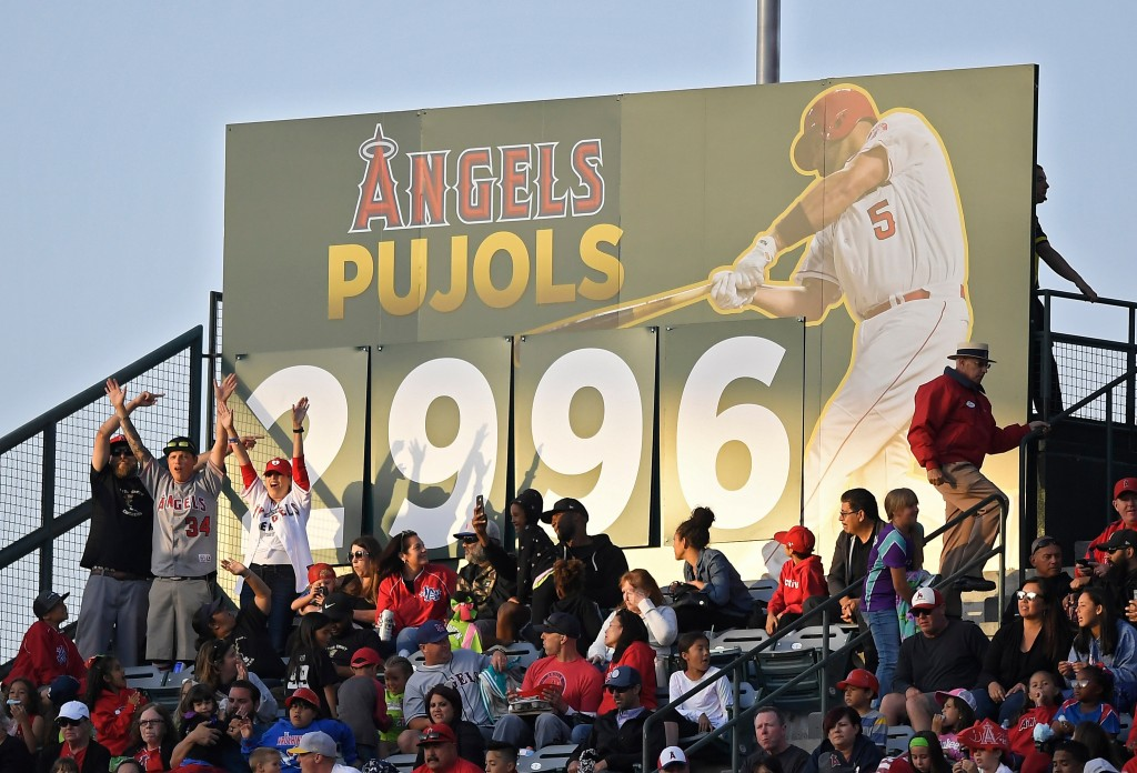 Fans cheer after Los Angeles Angels' Albert Pujols hit career hit 2,996 during the sixth inning of a baseball game against the New York Yankees, Sunda...