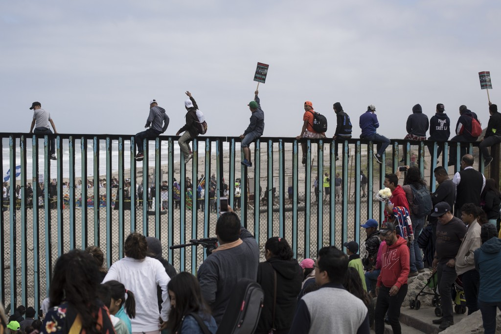 Central American migrants traveling with a caravan gather at the border wall, some sitting on top of it, look toward the U.S. from Mexico during a gat...