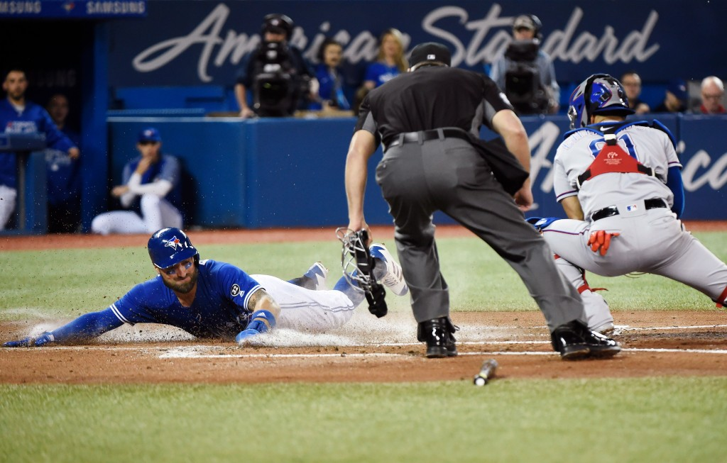 Toronto Blue Jays centre fielder Kevin Pillar (11) slides home safely ahead of the tag by Texas Rangers catcher Robinson Chirinos (61) on a sacrifice ...
