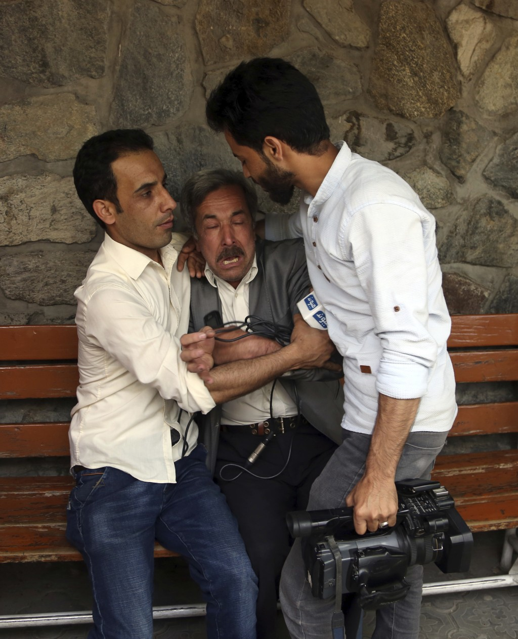 A man cries at a hospital after he lost his Journalist son in explosions in Kabul, Afghanistan, Monday, April 30, 2018. A coordinated double suicide b...
